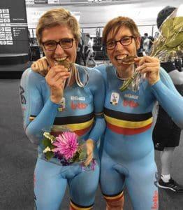 Twee paralympische atleten bijten op hun medaille.