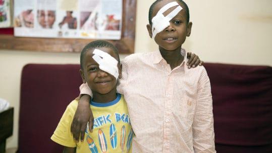 twee jongens met oogverband staan zij aan zijn.