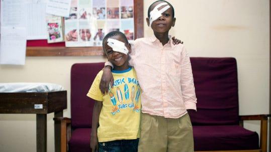twee jongens met oogverband omhelzen elkaar terwijl ze poseren voor de fotograaf