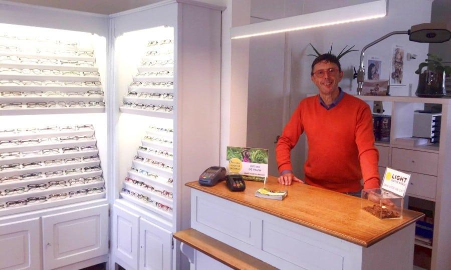 Optieker Chris De Pauw met feloranje trui staat achter zijn toonbank met het bordje van 'optieker van de wereld'
