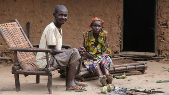 grootmoeder en vader zitten voor hun hutje