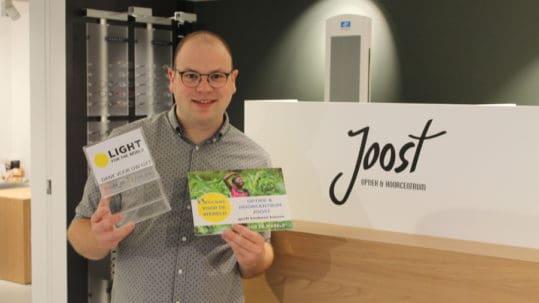 Opticien Joost toont trots zijn 'Opticien voor de Wereld' label.