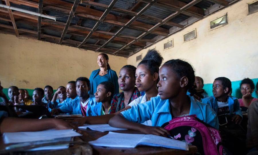 Light for the World's collega Yetnebersch staat in de midden van een klaslokaal met een tiental leerlingen.