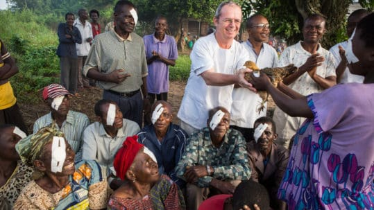 Dr. Richard ontvangt een kip van een patiente na een cataractoperatie.