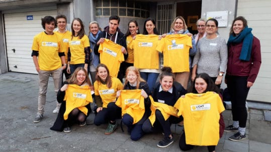 10 leerlingen en 6 leerkrachten met de knalgele licht voor de Wereld tshirt poseren voor ons gebouw.