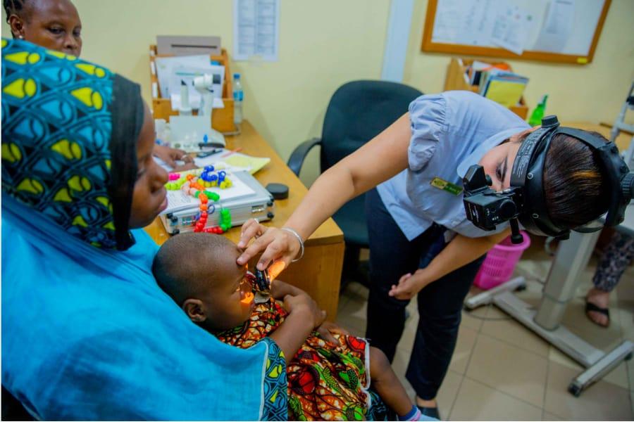 een oogartse onderzoekt een klein kindje.