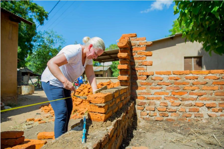 Een Belgische leerkrachte is een muurtje aan het metselen.