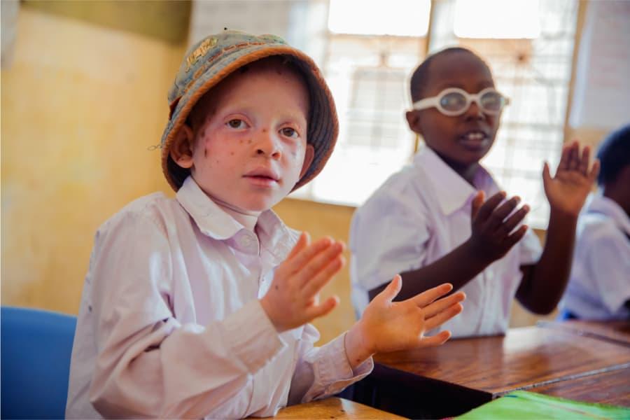 albino kindje en slechtziend kindje zitten naast elkaar en klappen in de handen.