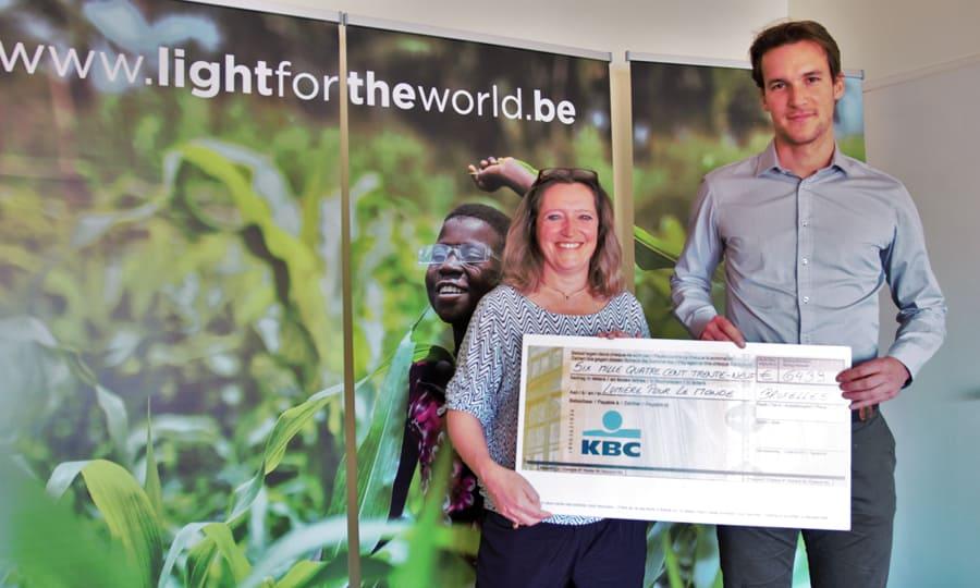 De zaakvoerder van Lucimed overhandigt de cheque aan de directeur van Licht voor de Wereld