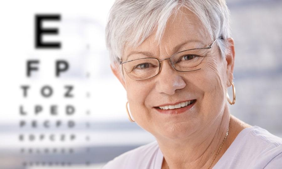 Oudere vrouw glimlacht met op de achtergrond een leestest.