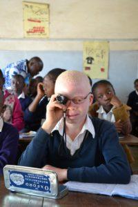 Een slechtziende albino-kind maakt gebruik van een vergrootglas