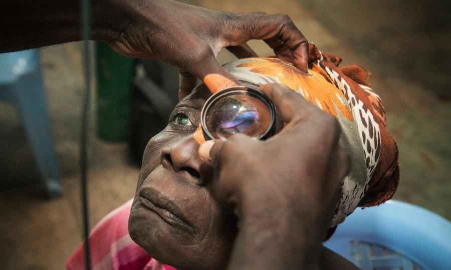 L'ophtalmologue examine les yeux d'une patiente.