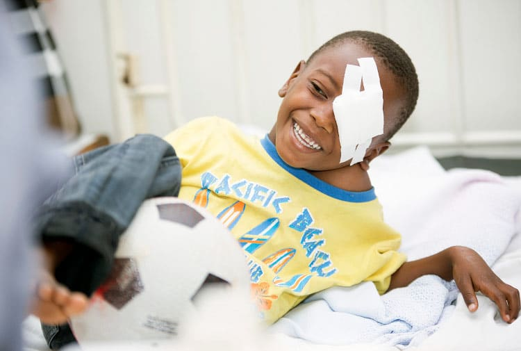 Garçon africain joyeux après opération oculaire